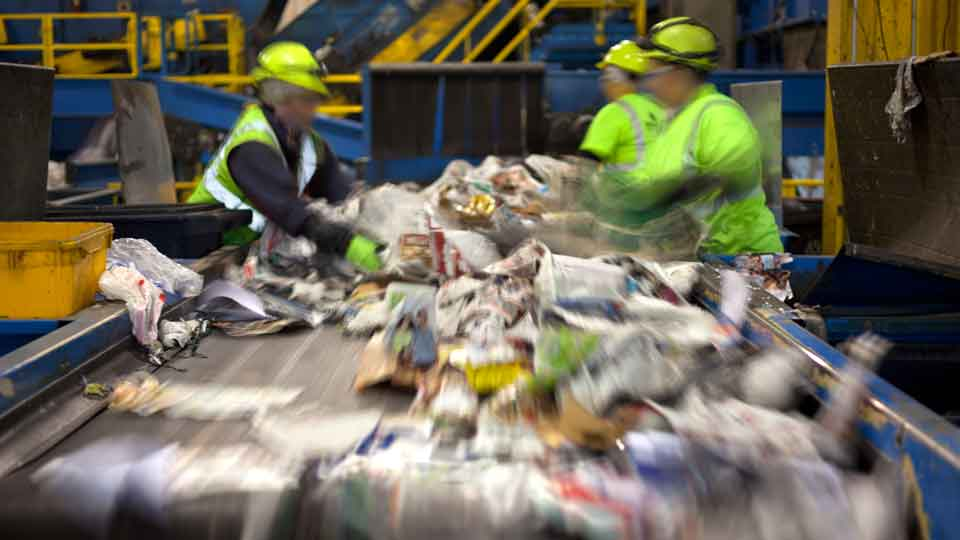 Workers sorting recycling at a municipal recycling facility (MRF)
